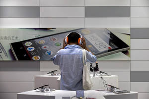 Photo - A man tries out a smartphone device on display at a Lenovo flagship experience store in Beijing, China Thursday, Aug. 15, 2013. Lenovo Group says it is evolving quickly into a supplier of wireless computing, driven by booming sales of smartphones and tablets as consumers shift away from desktop computers. (AP Photo/Andy Wong)