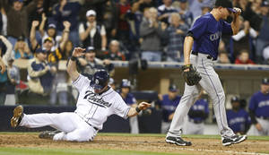 Photo - San Diego Padres' Seth Smith slides in with the go ahead run as Colorado Rockies relief pitcher Rex Brothers walks away after two runs scored on a wild pitch and a throwing error in the eighth inning of a baseball game won 5-4 by the Padres Monday, April 14, 2014, in San Diego. (AP Photo/Lenny Ignelzi