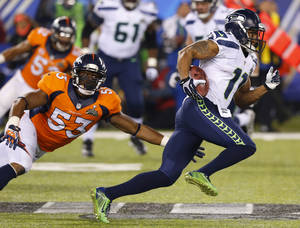 Photo - Seattle Seahawks' Percy Harvin sprints past Denver Broncos' Steven Johnson after an interception during the second half of the NFL Super Bowl XLVIII football game Sunday, Feb. 2, 2014, in East Rutherford, N.J. (AP Photo/Paul Sancya)