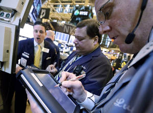 photo - Traders work on the floor Jan. 10 of the New York Stock Exchange. AP Photo