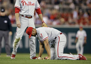 Photo - Philadelphia Phillies relief pitcher Luis Garcia, right, holds the ball after being hit by a two RBI single by Washington Nationals' Wilson Ramos, with second baseman Chase Utley, left, during the fifth inning of a baseball game at Nationals Park, Friday, Sept. 13, 2013, in Washington. (AP Photo/Alex Brandon)