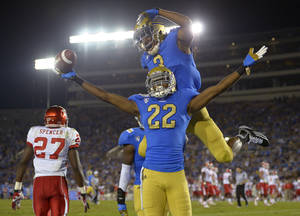 Photo -   UCLA cornerback Sheldon Price, lower right, celebrates along with cornerback Randall Goforth after intercepting the ball as Houston wide receiver Daniel Spencer walks away during the second half of their NCAA college football game, Saturday, Sept. 15, 2012, in Pasadena, Calif. (AP Photo/Mark J. Terrill)