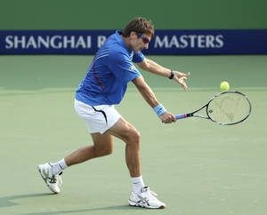 Photo -   Tommy Robredo of Spain returns a shot to Alex Bogomolov Jr. of Russia during the first round men's singles match of the Shanghai Masters tennis tournament at Qizhong Forest Sports City Tennis Center in Shanghai, China, Monday Oct. 8, 2012. Robredo won 7-6, 6-4. (AP Photo/Kin Cheung)