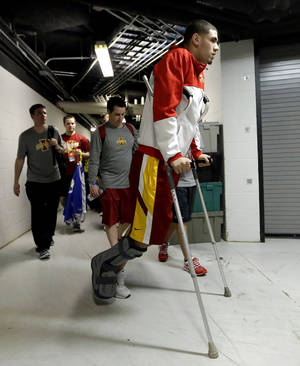 Photo - Iowa State's Georges Niang arrives at the AT&T Center using crutches for an NCAA college basketball tournament practice Saturday, March 22, 2014, in San Antonio. Niang, who broke his foot during Friday's game against North Carolina Central, with not play when Iowa State plays North Carolina Sunday. (AP Photo/David J. Phillip)