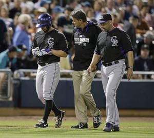 Photo - Colorado Rockies starting pitcher Tyler Chatwood leaves the field with trainer Keith Dugger and manager Walt Weiss after getting injured running for a triple during the third inning of an exhibition baseball game against the Seattle Mariners on Friday, March 28, 2014, in Peoria, Ariz. (AP Photo/Darron Cummings)