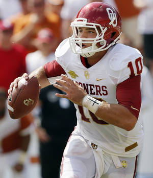 Photo - OU's Blake Bell (10) looks for a receiver during the Red River Rivalry college football game between the University of Oklahoma Sooners and the University of Texas Longhorns at the Cotton Bowl Stadium in Dallas, Saturday, Oct. 12, 2013. UT won, 36-20. Photo by Nate Billings, The Oklahoman