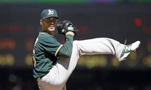 Photo - Oakland Athletics starting pitcher Scott Kazmir throws against the Seattle Mariners in the second inning of a baseball game Sunday, April 13, 2014, in Seattle. (AP Photo/Elaine Thompson)