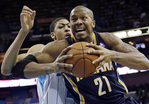 Photo - Indiana power forward David West (21) goes to the basket as New Orleans power forward Anthony Davis (23) defends in the first half of a NBA basketball game at the New Orleans Arena in New Orleans Saturday, Dec. 22, 2012. (AP Photo/Dave Martin