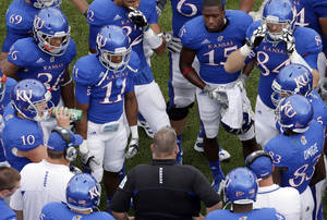 Photo -   FILE - In this Sept. 15, 2012, file photo, Kansas head coach Charlie Weis, bottom center, talks to his players during the second half of an NCAA college football game against TCU in Lawrence, Kan. Things are hardly off to the start that Weis expected in his first season at Kansas. Have there been signs of progress? Sure. But as a blowout loss to Kansas State can attest, the results have been the same as usual for the struggling Jayhawks. (AP Photo/Charlie Riedel, File)