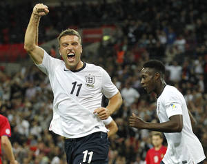 Photo - FILE - This is a Friday, Sept. 6, 2013 file photo of  England's Rickie Lambert celebrates after scoring a goal during the World Cup group H qualifier soccer match between England and Moldova at Wembley Stadium in London. England striker Rickie Lambert Monday June 2, 2014 joined Liverpool from Southampton for a reported fee of 4 million pounds ($6.7 million), strengthening the team's attacking options ahead of its return to the Champions League.  Released by his boyhood club as a 15-year-old, Lambert returns to Anfield after spending most of his career as a journeyman in England's lower leagues before making his name with Southampton since 2009.  (AP Photo/Sang Tan, File)