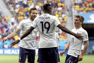 Photo - France's Paul Pogba (19) celebrates with teammates Yohan Cabaye, left, and Antoine Griezmann, right, after scoring his side's opening goal during the World Cup round of 16 soccer match between France and Nigeria at the Estadio Nacional in Brasilia, Brazil, Monday, June 30, 2014.  (AP Photo/David Vincent)