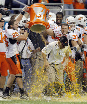 Photo - OSU head coach Mike Gundy is doused with Gatorade by Josh Cooper (25) and Bryant Ward (37) near the end of the Valero Alamo Bowl college football game between the Oklahoma State University Cowboys (OSU) and the University of Arizona Wildcats at the Alamodome in San Antonio, Texas, Wednesday, December 29, 2010. OSU won, 36-10. Photo by Nate Billings, The Oklahoman