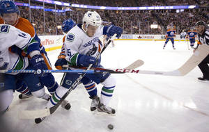 Photo - Vancouver Canucks' Jordan Schroeder works for the puck against Edmonton Oilers' Ryan Nugent-Hopkins, as Alexandre Burrows and Ladislav Smid lock up during the first period of an NHL hockey game Monday, Feb. 4, 2013, in Edmonton, Alberta. (AP Photo/The Canadian Press, Jason Franson)