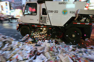 Photo - NEW YORK - JANUARY 1: A New York City Sanitation truck cleans up some of the tons of trash left by the revelers attending the New Years celebration  January 1, 2005 in Times Square in New York City. Close to 1 million people welcomed 2005 at the Times Square festivities.(Photo by Stephen Chernin/Getty Images)
