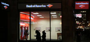 photo - In this Thursday, Dec. 13, 2012 photo people use a Bank of America ATM in Boston. Bank of America says its fourth-quarter earnings shrank as it cleaned up old problems from its mortgage unit.  The bank made $367 million in the last three months of 2012, down from $1.6 billion in the same period a year ago. The earnings were equivalent to 3 cents per share.  (AP Photo/Charles Krupa)