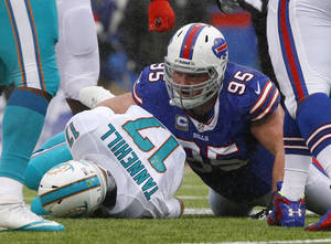 Photo - Buffalo Bills defensive tackle Kyle Williams (95) sacks Miami Dolphins quarterback Ryan Tannehill (17) during the first half of an NFL football game on Sunday, Dec. 22, 2013, in Orchard Park, N.Y. Buffalo won 19-0. (AP Photo/Bill Wippert)