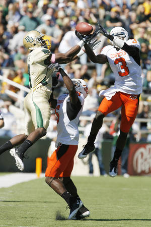 Photo - Baylor's David Gettis, left, and OSU's Victor Johnson go up for a pass during OSU's win over Baylor. Johnson injured his knee this week in practice and will likely miss the rest of the season. Photo by STEVE SISNEY THE OKLAHOMAN