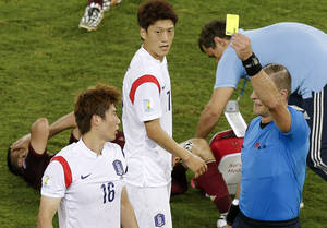 Photo - Referee Nestor Pitana from Argentina, right, books South Korea's Ki Sung-yueng (16) after a foul during the group H World Cup soccer match between Russia and South Korea at the Arena Pantanal in Cuiaba, Brazil, Tuesday, June 17, 2014. (AP Photo/Thanassis Stavrakis)