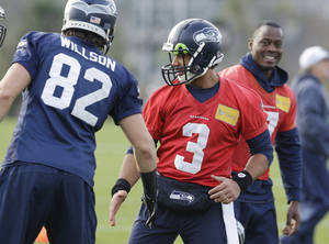 Photo - Seattle Seahawks quarterback Russell Wilson (3) greets tight end Luke Willson (82) at the start of NFL football practice on Wednesday, Jan. 15, 2014, in Renton, Wash. The Seahawks are to play the San Francisco 49ers on Sunday in the NFC championship. (AP Photo/Ted S. Warren)