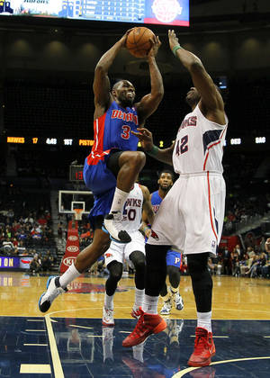 Photo - Detroit Pistons guard Rodney Stuckey (3) goes up for the shot against Atlanta Hawks forward Elton Brand (42) in the first period in an NBA basketball game in Atlanta, Tuesday, April 8, 2014. (AP Photo/Todd Kirkland)