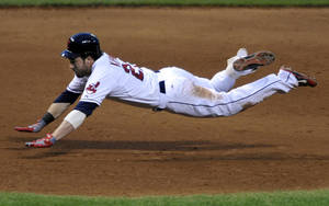 Photo - Cleveland Indians' Jason Kipnis slides into third base with a triple in the fourth inning of a baseball game against the Minnesota Twins, Saturday, June 22, 2013, in Cleveland. (AP Photo/David Richard)