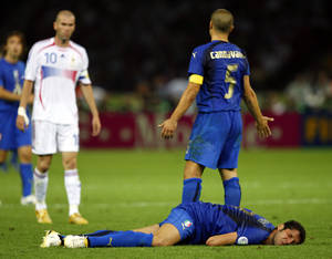 Photo - FILE - In this Sunday, July 9, 2006, file photo, France's Zinedine Zidane, left, looks on as Italy's Marco Materazzi lies injured, and Italy's Fabio Cannavaro reacts, during extra time in the World Cup final soccer match between Italy and France, at the Olympic Stadium, in Berlin. On this day: Zidane is sent off minutes before the end of the final after head-butting Italy defender Materazzi. Italy wins ensuing penalty shoot-out to claim its fourth World Cup. (AP Photo/Jasper Juinen, File)