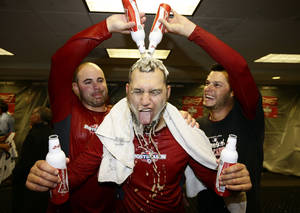 Photo -   Members of the St. Louis Cardinals celebrate in the locker room after Game 5 of the National League division baseball series against the Washington Nationals on Saturday, Oct 13, 2012, in Washington. St. Louis won 9-7. (AP Photo/Alex Brandon)