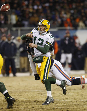 Photo - Green Bay Packers quarterback Aaron Rodgers (12) gets hit from behind  by Chicago Bears defensive end Julius Peppers as he gets off a pass during the first half of an NFL football game, Sunday, Dec. 29, 2013, in Chicago. (AP Photo/Charles Rex Arbogast)