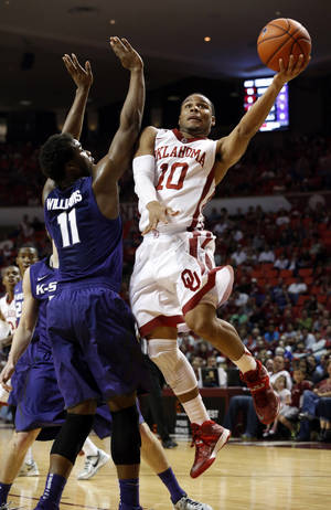 Photo - Oklahoma's Jordan Woodard (10) shoots past Kansas State's Nino Williams (11) during the first half of an NCAA college basketball game Saturday, Feb. 22, 2014, in Norman, Okla.  (AP Photo/The Oklahoman, Steve Sisney)
