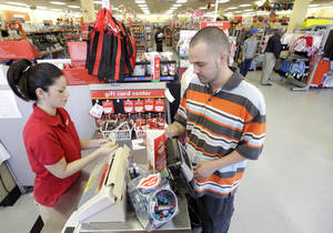 Photo - Family Dollar employee Pam ela Ramos assists John Conner with a purchase at a store in Waco, Texas.  AP File Photo <strong>Tony Gutierrez -   </strong>