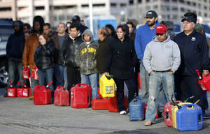 photo -   People line up at a gas station waiting to fill up, Friday, Nov. 2, 2012, in Newark, N.J. In parts of New York and New Jersey, drivers lined up early Friday for hours at gas stations that were struggling to stay supplied. The power outages and flooding caused by Superstorm Sandy have forced many gas stations to close and disrupted the flow of fuel from refineries to those stations that are open. (AP Photo/Julio Cortez)