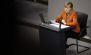 Photo - German Chancellor Angela Merkel speaks during a government statement as part of a meeting of the German federal parliament, Bundestag, in Berlin, Germany, Wednesday, Jan. 29, 2014. Due to a hip injury Merkel has to sit during her speech. The reflections are caused by windows at the visitors tribune.  (AP Photo/Michael Sohn)