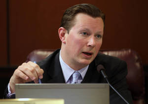 photo - Nevada Sen. Ben Kieckhefer, R-Reno, works in committee at the Legislative Building in Carson City, Nev., on Thursday, Feb. 14, 2013. Kieckhefer introduced a measure that would prevent mentally ill people from purchasing firearms for at least three years after the court is informed of a diagnosis. (AP Photo/Cathleen Allison)