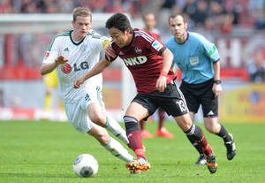 Nuremberg's Hiroshi Kiyotake, right,and Leverkusen's Lars Bender vie for the ball during the German Bundesliga soccer match between 1. FC Nuremberg and Bayer 04 Leverkusen at Grundig-Stadion in Nuremberg, Germany, April 20, 2014. (AP Photo/dpa/Timm Schamberger)