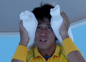 Photo - Kei Nishikori of Japan wraps an ice pack around his head during a break in his first round match against Marinko Matosevic of Australia at the Australian Open tennis championship in Melbourne, Australia, Tuesday, Jan. 14, 2014.(AP Photo/Aaron Favila)