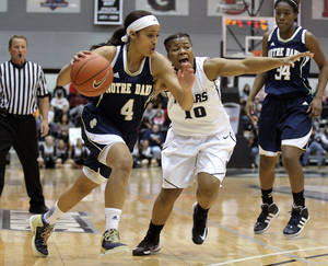photo - Notre Dame guard Skylar Diggins (4) is defended by Providence guard Danielle Pearson (10) during first-half action in an NCAA college basketball game Saturday, March 2, 2013, in Providence, R.I. (AP Photo/Stew Milne)