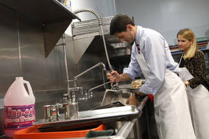 Photo -   Republican vice presidential candidate, Rep. Paul Ryan, R-Wis., and his wife Janna wash pots at St. Vincent DePaul dinning hall, Saturday, Oct. 13, 2012 in Youngstown, Ohio. (AP Photo/Mary Altaffer)