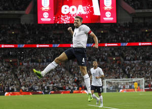Photo - England's Steven Gerrard jumps to celebrate scoring a goal during the World Cup group H qualifier soccer match between England and Moldova at Wembley Stadium in London, Friday, Sept. 6, 2013. (AP Photo / Sang Tan)
