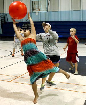 Photo - Kaia Lavastida, 11, reaches for a ball during a game Friday at a city-sponsored fall break camp at Irving Recreation Center in Norman. PHOTO BY STEVE SISNEY, THE OKLAHOMAN <strong>STEVE SISNEY</strong>