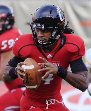 Photo -   In this Nov. 12, 2011 photo, Cincinnati quarterback Munchie Legaux rolls out in the second half of an NCAA college football game against West Virginia, in Cincinnati. Legaux will start this Saturday at Rutgers after starting quarterback Zach Collaros suffered a broken ankle against West Virginia. (AP Photo/Al Behrman)