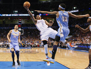 photo - Oklahoma City&#039;s Russell Westbrook (0) goes to the basket between Denver&#039;s JaVale McGee (34) and Corey Brewer (13) during the NBA basketball game between the Oklahoma City Thunder and the Denver Nuggets at Chesapeake Energy Arena in Oklahoma City, Wednesday, April 25, 2012. Oklahoma City lost 106-101.  Photo by Bryan Terry, The Oklahoman