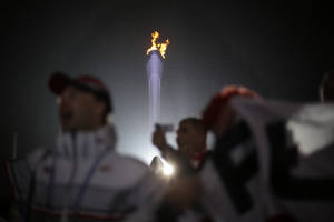 Photo - Fans cheer near the Olympic flame while watching the medals ceremonies at the 2014 Winter Olympics, Sunday, Feb. 16, 2014, in Sochi, Russia. (AP Photo/David Goldman)