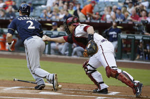Photo - Arizona Diamondbacks' Miguel Montero, right, tags Milwaukee Brewers' Scooter Gennett (2) out after the third strike was dropped by Montero during the first inning of a baseball game on Monday, June 16, 2014, in Phoenix. (AP Photo/Ross D. Franklin)