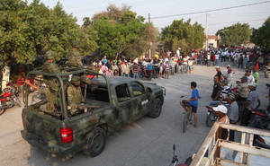 Photo - Mexican army soldiers enter the town of La Ruana, Michoacan, Mexico, Monday, May 20, 2013. Residents of western Mexico towns who endured months besieged by a drug cartel are cheering the arrival of hundreds of Mexican army troops. A growing number of people in the state of Michoacan have taken up arms to defend their villages against drug gangs, a vigilante movement born of frustration at extortion, killings and kidnappings in a region wracked by violence. (AP Photo/Marco Ugarte)