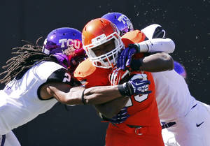 Photo - FILE - In this Oct. 19, 2013, file photo, Oklahoma State running back Rennie Childs (23) fights off a tackle by TCU cornerback Jason Verrett (2) and safety Chris Hackett (1) during the fourth quarter of an NCAA college football game in Stillwater, Okla. Childs provided Oklahoma State with a much-needed boost on the ground in last week's win over TCU. The running back could be counted on again this week when the Cowboys travel to Iowa State. (AP Photo/Sue Ogrocki, File)