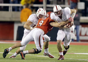 Photo - Utah's Trevor Reilly (9) tackles Stanford quarterback Kevin Hogan, right, during the fourth quarter of an NCAA college football game on Saturday, Oct. 12, 2013, in Salt Lake City. (AP Photo/Rick Bowmer)