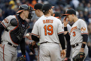 Photo - Baltimore Orioles catcher Matt Wieters, left, leans in as starting pitcher Ubaldo Jimenez leaves the mound before giving the ball to Baltimore Orioles manager Buck Showalter in the fifth inning of a baseball game against the New York Yankees at Yankee Stadium in New York, Monday, April 7, 2014. Baltimore Orioles first baseman Chris Davis (19) and Baltimore Orioles second baseman Ryan Flaherty (3) join the team on the mound. (AP Photo/Kathy Willens)