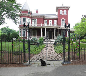 Photo -  A black cat sits at the front gate at the home of writer Stephen King in Bangor, Maine. Photo courtesy of Jerry Farlow.