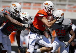 photo - OKLAHOMA STATE UNIVERSITY / OSU / COLLEGE FOOTBALL: OSU's Charlie Moore runs past Jimmy Bean, left, Miketavius Jones, and Cameron Gravelle, right, on his way to a touchdown during Oklahoma State's spring football game at Boone Pickens Stadium in Stillwater, Okla., Saturday, April 21, 2012. Photo by Bryan Terry, The Oklahoman