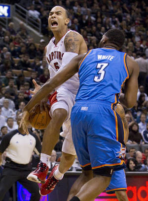 Photo - The Raptors' Jerryd Bayless, left, shouts while being fouled by the Thunder's D.J. White during Friday's game in Toronto. AP Photo